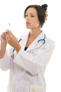 Doctor or nurse with medical syringe