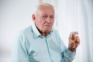 Senior male patient holding urin sample