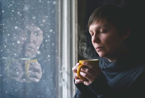 Lonesome Woman Drinking Coffee in Dark Room