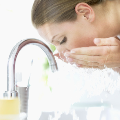 close-up of a young woman washing her face