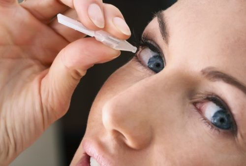 Woman adding eyedrops