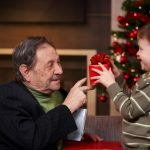 Small boy giving present to grandfather at christmas
