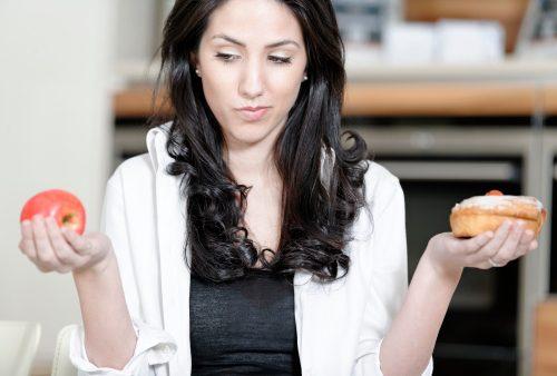 Woman choosing cake or fruit