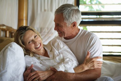 Senior couple embracing in bed, smiling, close-up