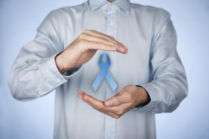 Prostate cancer awareness - man with protective and support gesture and blue ribbon.