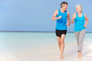 Senior Couple Running On Beautiful Beach