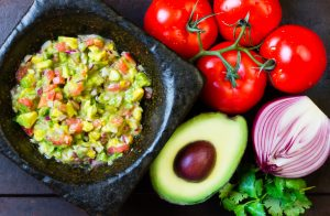 Guacamole in stone mortar and ingredients. Top view