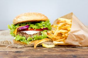 Photo of double hamburger with fries, tomatoes and saladon wooden surface