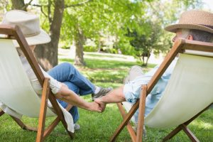 Mature couple sitting in deck chairs at park