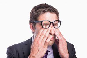 Closeup of a worried businessman rubbing eyes