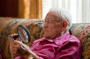 Elderly old man using magnifying glass to read fine print on object with strong light over shoulder while wearing glasses.