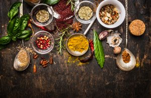Dry colorful spices with fresh seasoning on rustic wooden background