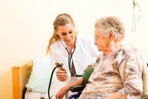 Young female nurse checking elderly woman's blood pressure