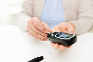 senior woman with glucometer checking blood sugar
