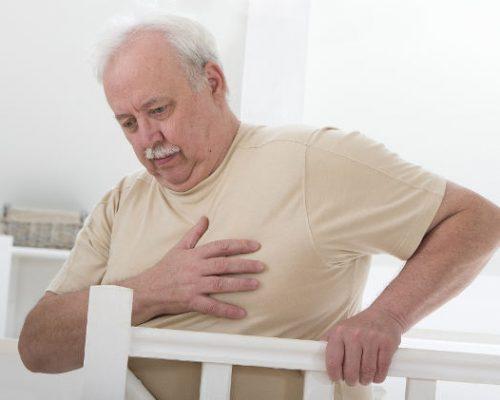 oerweight senior man' hand grabbing his chest
