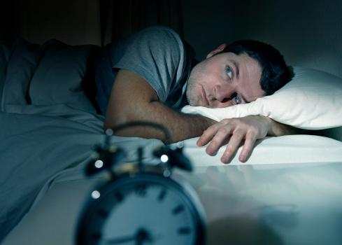 man in bed eyes opened suffering from sleep apnea