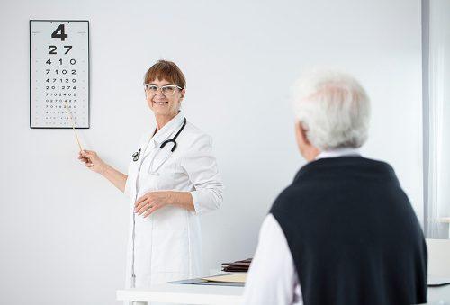Oculist examining eye of an elderly man