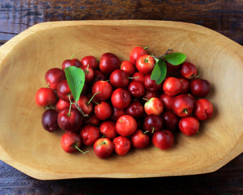 Acerola Cherry raw, fresh, in wooden trough on rustic wooden table, antioxidant fruits. Top View