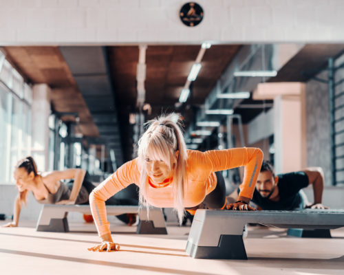 Group of sporty people doing push ups on steppers in gym. Selective focus on blonde woman, in background mirror.