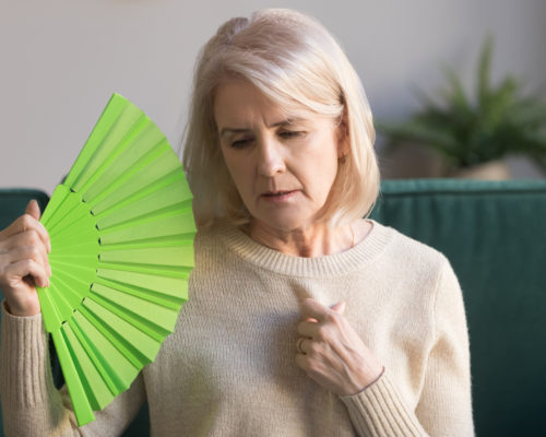 Overheated elderly woman sitting on couch waving green fan to cool herself, sixty years female feels unwell hot, age hormonal changes, apartments without air conditioner, summertime discomfort concept