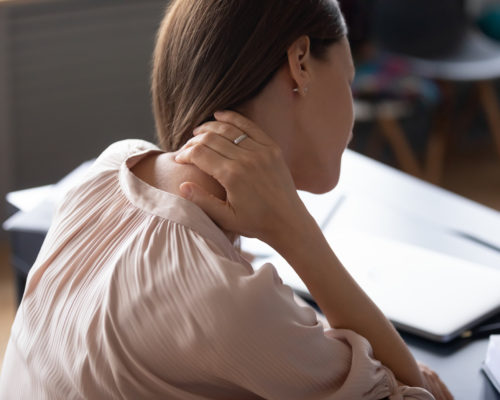 Back view of young woman touch neck suffer from sudden muscular spasm at workplace, unwell millennial female worker massage upper back having backache or pinched nerves sitting in incorrect posture