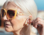 Senior woman puts on the hearing aid. Deafness, senior health care concept