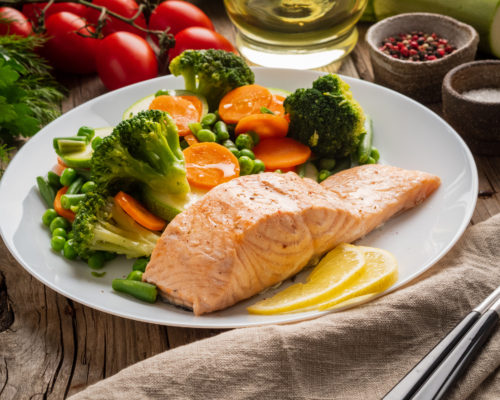 Steam salmon and vegetables, Paleo, keto, fodmap diet. White plate on old rustic wooden table, side view