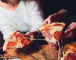 High angle shot of a group of unrecognizable people's hands each grabbing a slice of pizza
