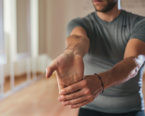 Sporty man stretching forearm before gym workout. Fitness strong male athlete standing indoor warming up.