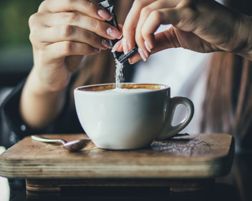 The girl's hand pours sugar into her coffee. Close up.