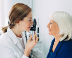 Doctor Optometrist examining senior woman's eye with ophthalmoscope