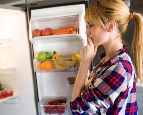 Shot of pretty young woman hesitant to eat in front of the fridge in the kitchen.