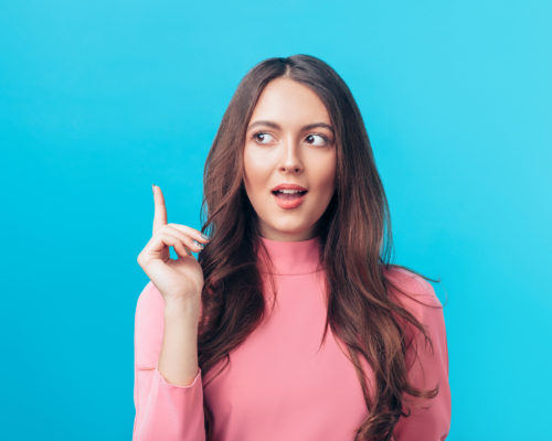 Young beautiful woman having good idea with her finger pointing up isolated on blue background. Success, idea and innovation concept.