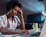 Displeased black healthcare worker using computer and reading an e-mail at doctor's office.