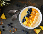 Healthy pineapple, mango smoothie bowl with coconut, bananas, blueberries and granola. Top view table scene on a dark background.