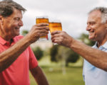 Two senior men toasting beer glasses outdoors. Smiling mature male friends cheering beers while standing outside.