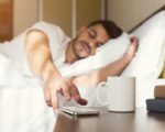 Sleepy guy waking up early after hearing alarm clock signal on smartphone on monday morning, reaching for ringing mobile phone with closed eyes, copy space