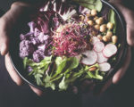Healthy dinner, lunch. Man eating vegan superbowl or Buddha bowl with vegetables, fresh salad, chickpeas, soybean sprouts, purple broccoli. Сlean eating, vegan concept