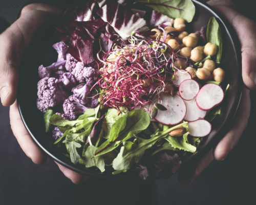 Healthy dinner, lunch. Man eating vegan superbowl or Buddha bowl withvegetables, fresh salad, chickpeas, soybean sprouts, purple broccoli. Сlean eating, vegan concept