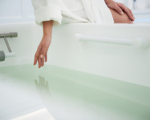 Health treatment concept. Close up portrait of young woman touching water in bath tub before water spa procedure