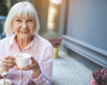 Waist up portrait of happy elderly woman sitting at table in cafe and holding cup of tea. She is enjoying evening on her own. Copy space in right side