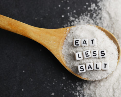 Eat less salt advice written with plastic letter beads on granulated salt – healthy food lifestyle