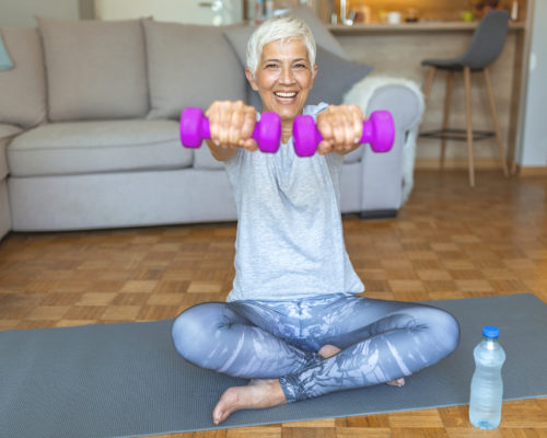 Portrait of mature fitness woman lifting dumbbells. Portrait of happy senior woman holding dumbbell at home. Active senior woman exercising with dumbbell at home