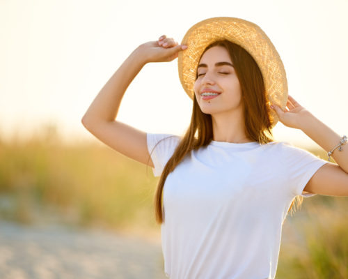 Spa wellness beach beauty woman relaxing and sun bathing on beach in straw hat. Beautiful serene and peaceful young female model with teeth braces on holiday travel resort enjoting vacation. Flower in braided hair.