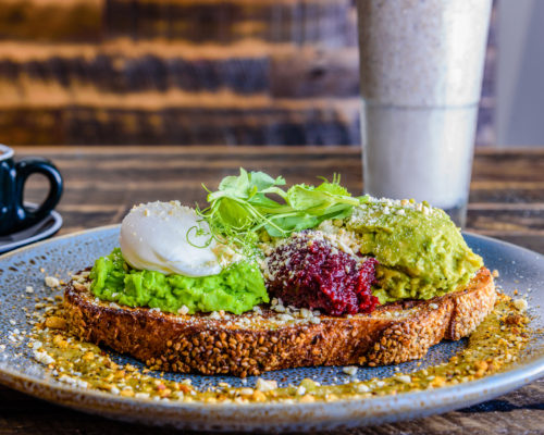 A plate of smashed avocado on toast with a poached egg on top