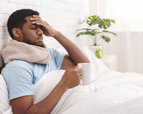Feeling bad. Sick african-american man drinking hot healing tea in bed, touching his forehead, empty space