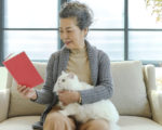 Senior lady, Adult, Pets, Clothing, Embracing, Holding a cat and reading a book.