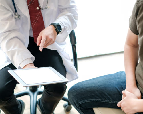 Doctor holding digital tablet talk and explain about the treatment of male patients. Treating patients with prostate cancer.