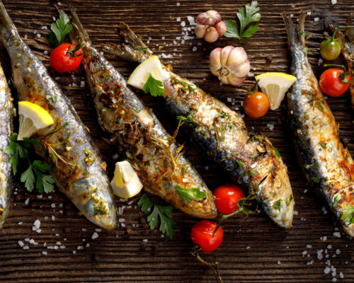 Fried fishes with addition of herbs, spices and lemon slices on a wooden background. Seafood, sardines
