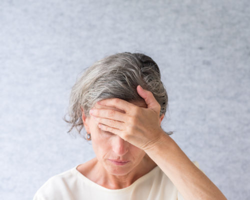 Closeup of middle aged woman looking down with hand over forehead against grey background (selective focus)